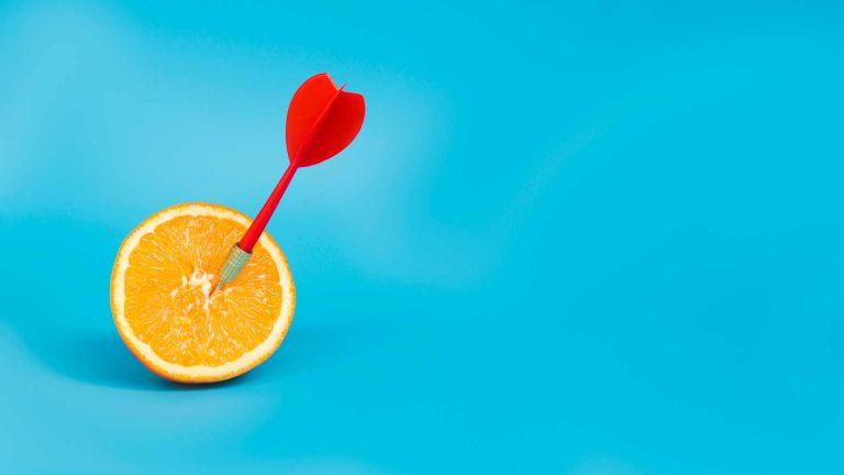 kuvassa sinisellä taustalla appelsiinin puolikas, johon nuoli on osunut juuri keskelle