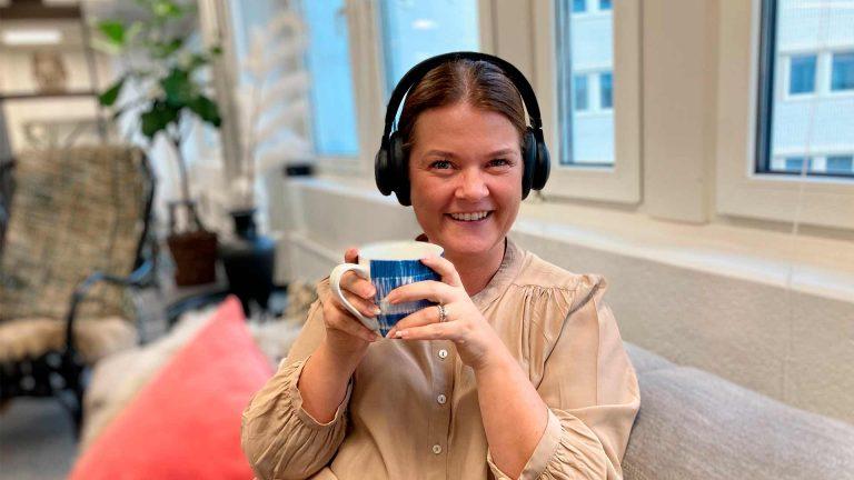 nainen istuu sohvalla, hymyilee ja kuuntelee podcasteja ja pitää kahvikuppia kädessään