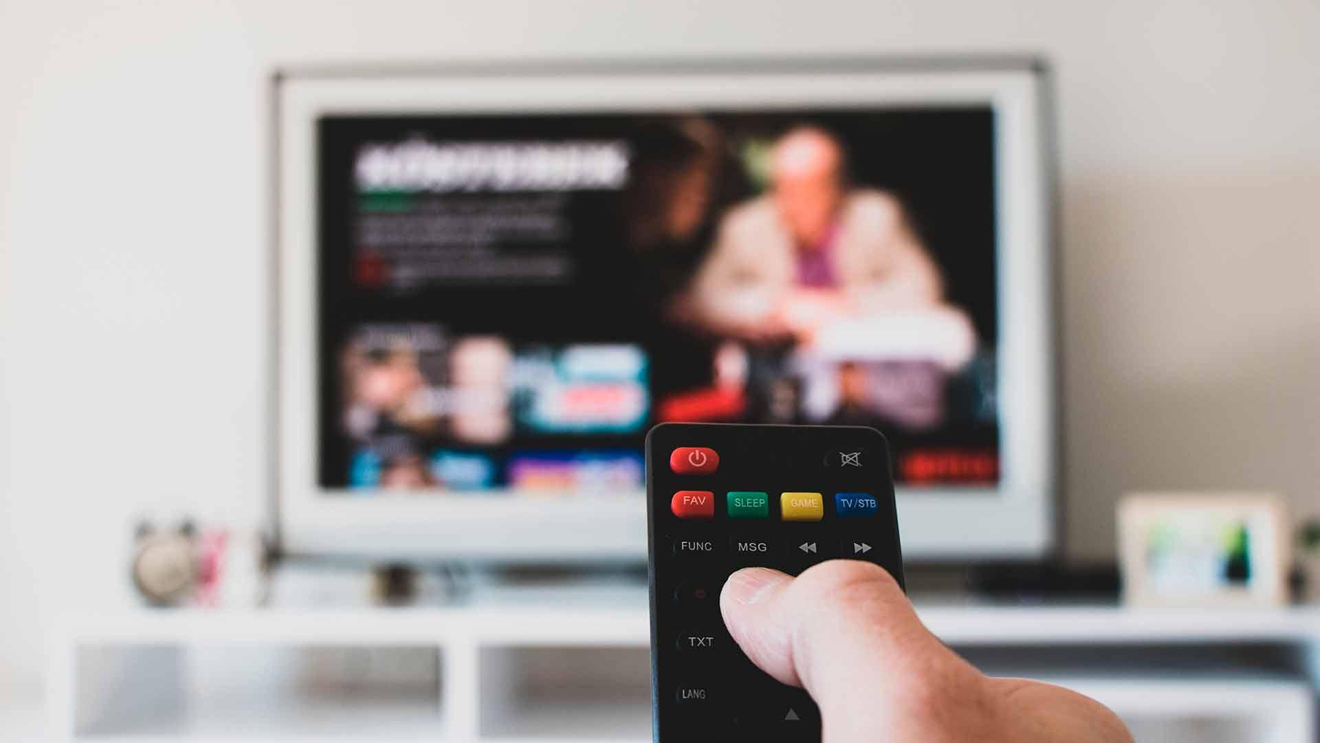kuvan etualalla on kaukosäädin kädessä ja taustalla näkyy tv, josa auki suoratoistopalvelu